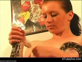 Ponytailed babe masturbates and shoves snake in her cooch
